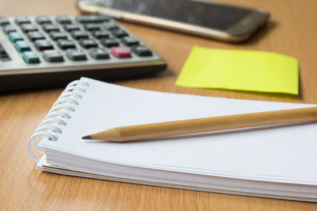 cuadro sinoptico: Note paper, pencil, notepad, calculator and mobile phone Foto de archivo