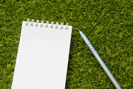 blue pen: Notepad with blue pen on artificial green grass
