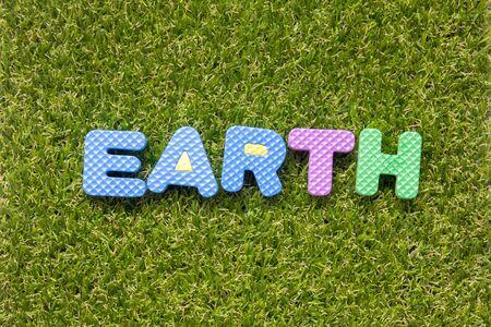 Toy foam in word earth on green grass backgroun Imagens