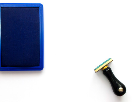 secretary tray: Black wooden rubber stamp with blue ink tray on white background Stock Photo