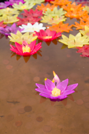 Colorful candle in lotus shape floating on water