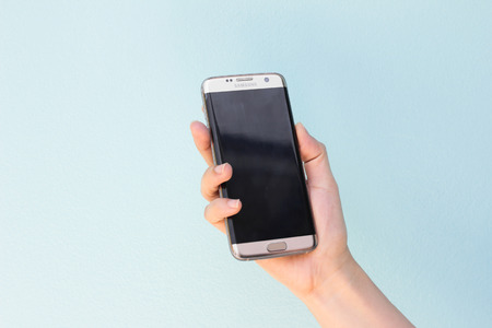 samsung galaxy: Bangkok, Thailand September 10, 2016 : Woman held android phone Samsung galaxy S7 Edge on blue concrete background. Samsung S7 Edge is smart phone with multi touch screen Editorial