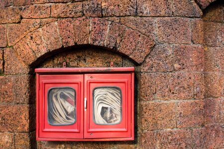 quell: Fire hose in red box on brick wall background Stock Photo