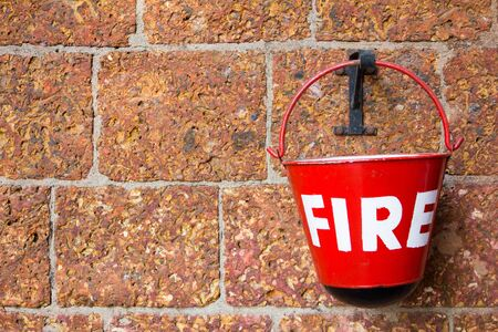quell: Red fire bin contain the sand on brick wall background Stock Photo