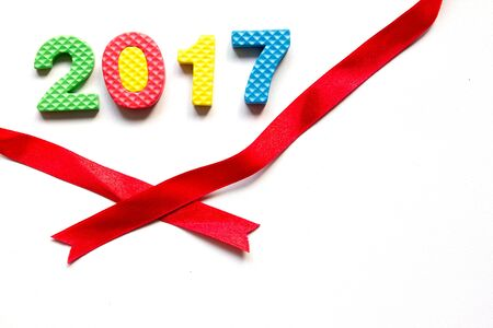 Wording 2017 from toy alphabet with red ribbon on white background (Concept of Happy new year)
