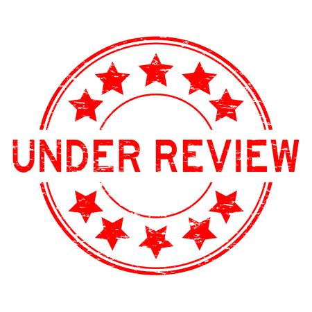 Grunge rojo bajo revisión con icono de estrella ronda sello de goma