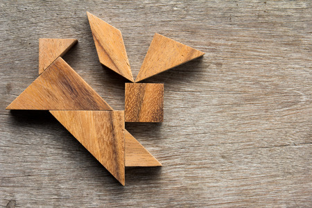 silhouette lapin: Wooden tangram as running rabbit shape on old wood background Banque d'images