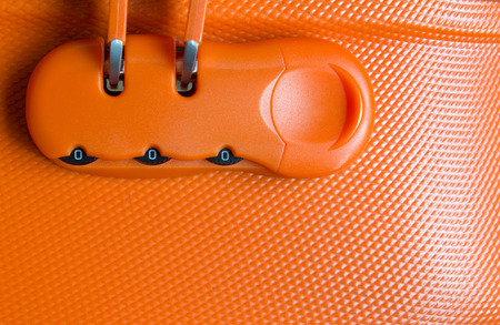 Closed up password lock of orange luggage background