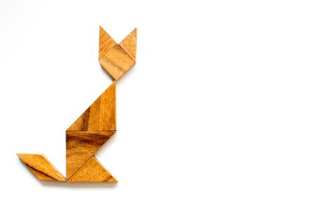 Wooden tangram as waiting cat shape on white background