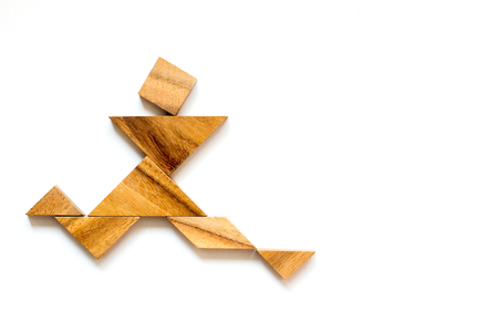Wooden tangram as running man shape on white background