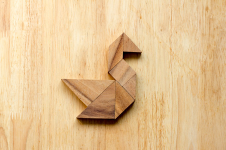 completed: Tangram puzzle in swan shape on wooden background Stock Photo