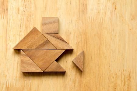 Tangram puzzel in huisvorm met het ontbrekende stuk op houten achtergrond (Concept voor droomhuis) Stockfoto