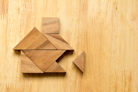 Tangram puzzle in home shape with the missing piece on wooden background (Concept for dream home) Archivio Fotografico