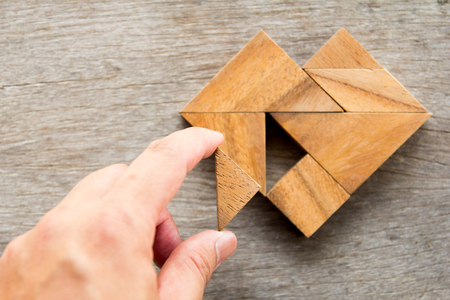 completed: Man held piece of tangram puzzle to fulfill the heart shape on wooden table