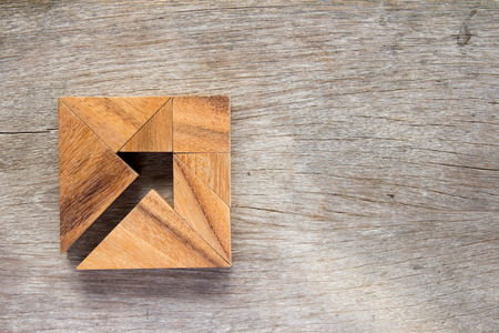 jigsaw tangram: Tangram puzzle as arrow in square shape on wooden background (Concept for business direction and decision) Stock Photo