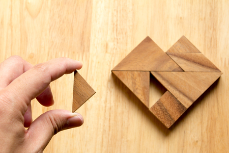 inventive: Man held piece of tangram puzzle to fulfill the heart shape on wooden table (Concept of love) Stock Photo
