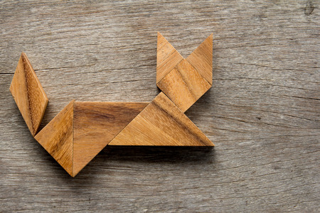 Chinese tangram puzzle in cat sitting shape on wooden background