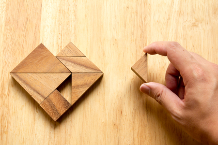 completed: Man held piece of tangram puzzle to fulfill the heart shape on wooden table (Concept of love) Stock Photo
