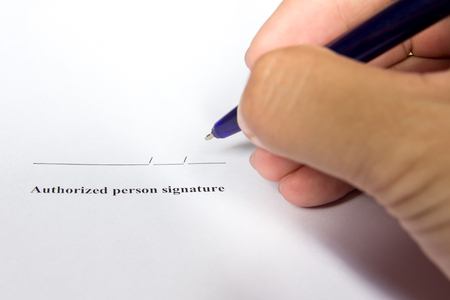Business man hold the pen for sign in authorization signature space background Stock Photo