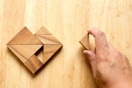 fulfill: Man held piece of tangram puzzle to fulfill the heart shape on wooden table (Concept of love) Stock Photo