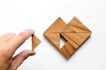 Man aangehouden stuk tangram puzzel om de hartvorm op een witte achtergrond te vervullen (Concept van de liefde)