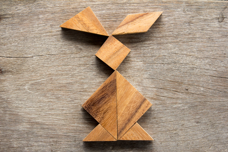 silhouette lapin: Chinese tangram puzzle in rabbit shape on wooden background (Concept for easter)