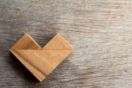 jigsaw tangram: Tangram puzzle in heart shape on wooden background Stock Photo