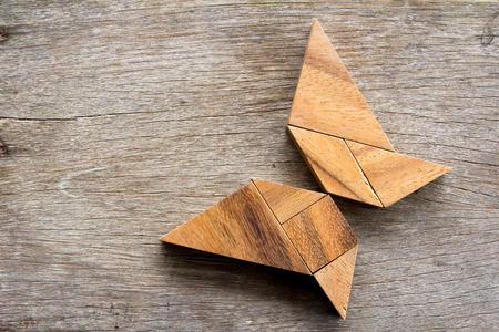 silhouette papillon: Wooden tangram puzzle in flying butterfly shape background Banque d'images