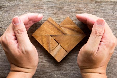 jigsaw tangram: Hand cover tangram puzzle in heart shape on wooden background Stock Photo