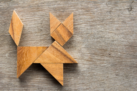 Chinese tangram puzzle in cat shape on wooden background