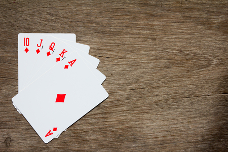 Five card of red diamond royal straight flush on wooden background Foto de archivo