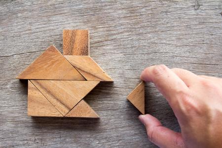 木製タングラム パズル待機ビルド夢家または幸せな人生コンセプト ホーム形状を満たすために