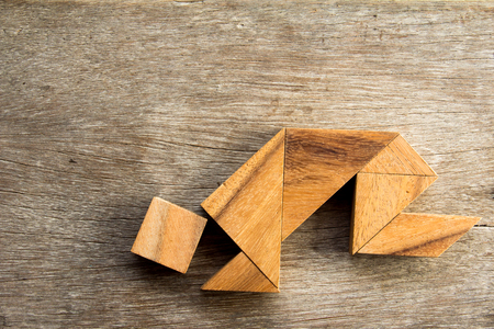 crouch: Wooden tangram puzzel in man crouch shape background Stock Photo