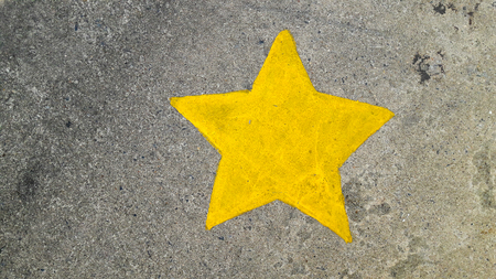 shiny floor: Yellow painting star on concrete texture background