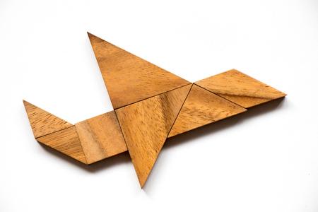 Houten tangram puzzel in de vorm van een vliegtuig op een witte achtergrond (Concept voor nieuwe ervaring, start project) Stockfoto