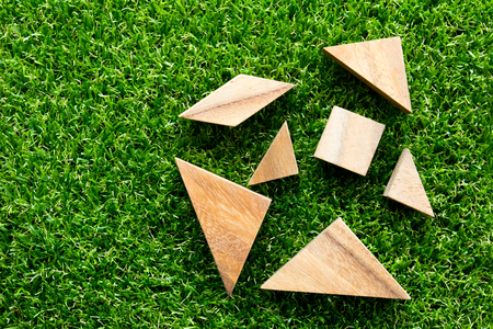 Wooden tangram puzzle wait for complete on artificial green grass background