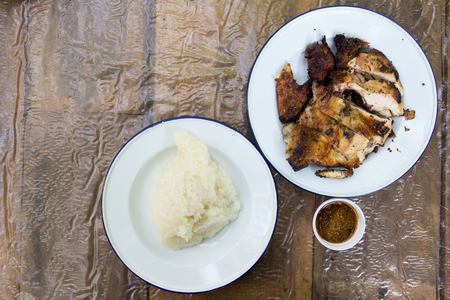 piri: Grilled chicken and sticky rice on wooden background