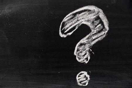 Kreda rysunek jako kształt znaku zapytania na tle czarnej tablicy