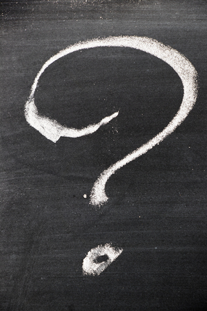 answer: Chalk hand drawing as question mark shape on black board background