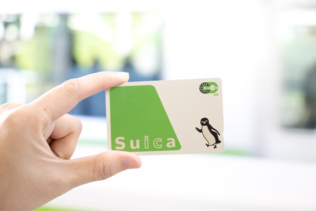 Tokyo, Japan - April 23, 2017 : Man hold Suica pass with the blurred background, Suica is a prepaid card for travelling with train, bus and shopping in Japan. 에디토리얼