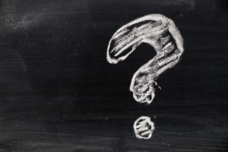Chalk hand drawing as question mark shape on black board background