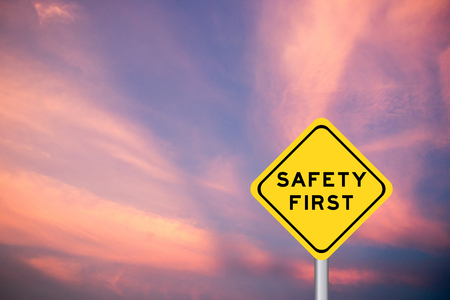 Safety first wording on yellow transportation sign with violet cloud sky background Stock Photo