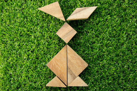 Wooden tangram puzzle in rabbit shape on artificial green grass background (Concept of Happy Easter) Stock Photo
