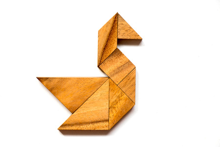 Wooden tangram puzzle in swan shape on white background Stock Photo