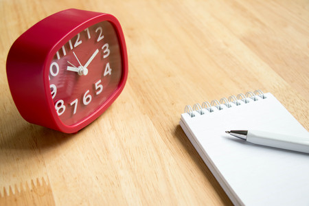 appointment book: Note book with pen and red clock on wooden table background