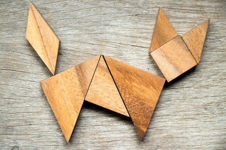 Tangram puzzle in cat shape on wooden background