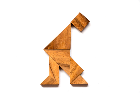 Wooden tangram puzzle in man sit and think shape on white background