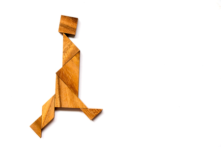 Wooden tangram puzzle in walking man shape on white background Stock Photo