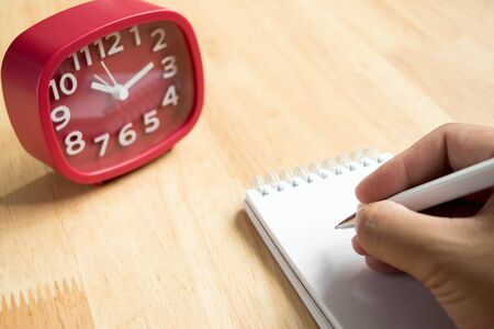appointment book: Man hold the pen with book and red clock on wooden table background