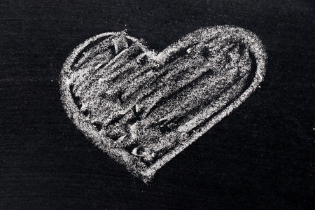 White chalk drawing in heart shape on black board background use for decoration in valentine, love, couple or engagement concept